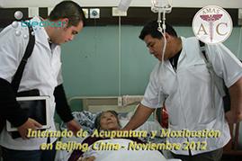 dos participantes del curso de acupuntura visitan a una paciente durante las practicas de acupuntura en el  hospital